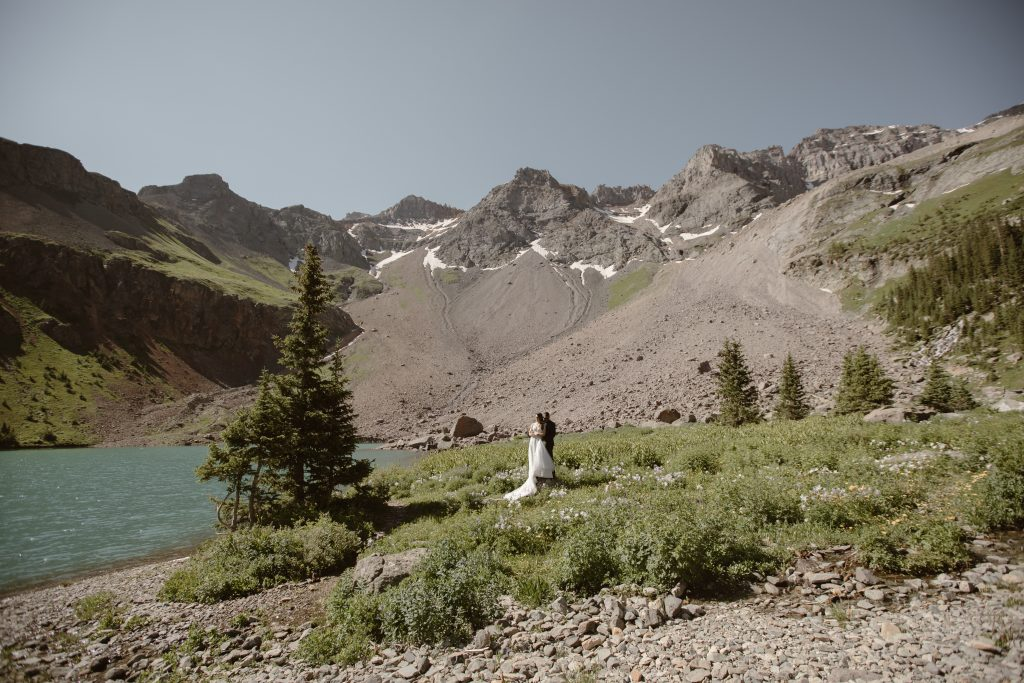 a couple standing next to an alpine lake