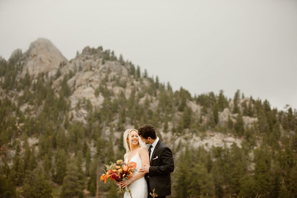 a bride and groom laughing together while wearing wedding clothes with a evergreen mountain in the background