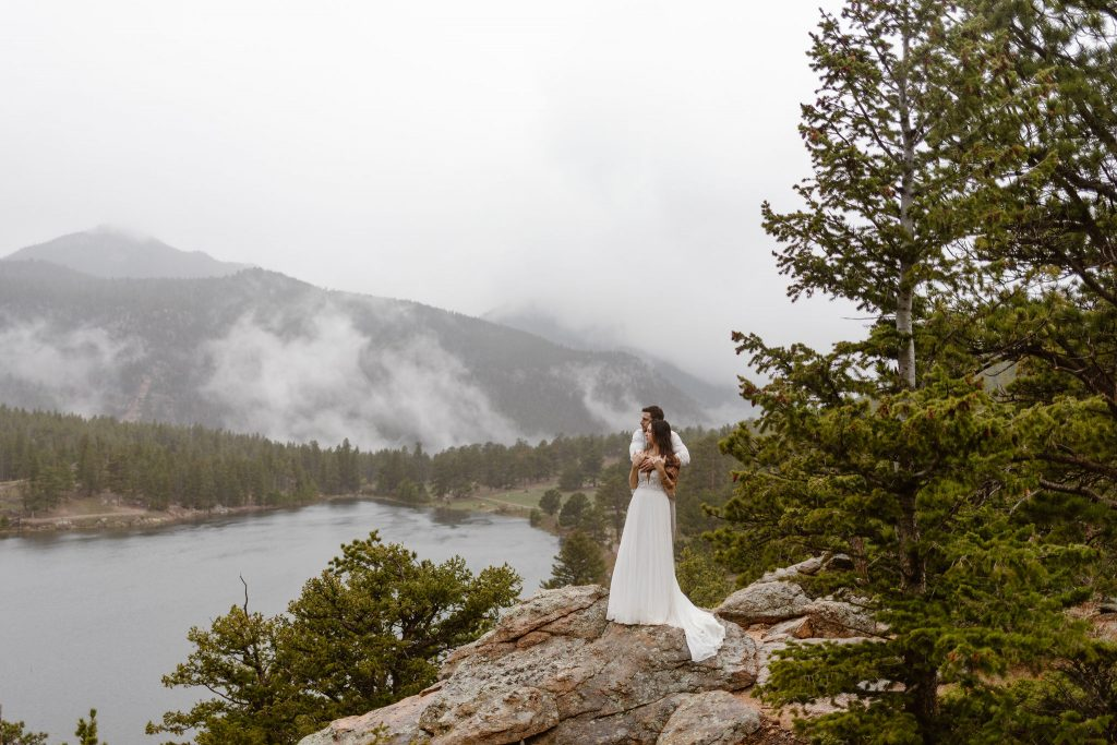 a couple standing on a rock on an overlook in rocky mountain national park while wearing wedding clothes