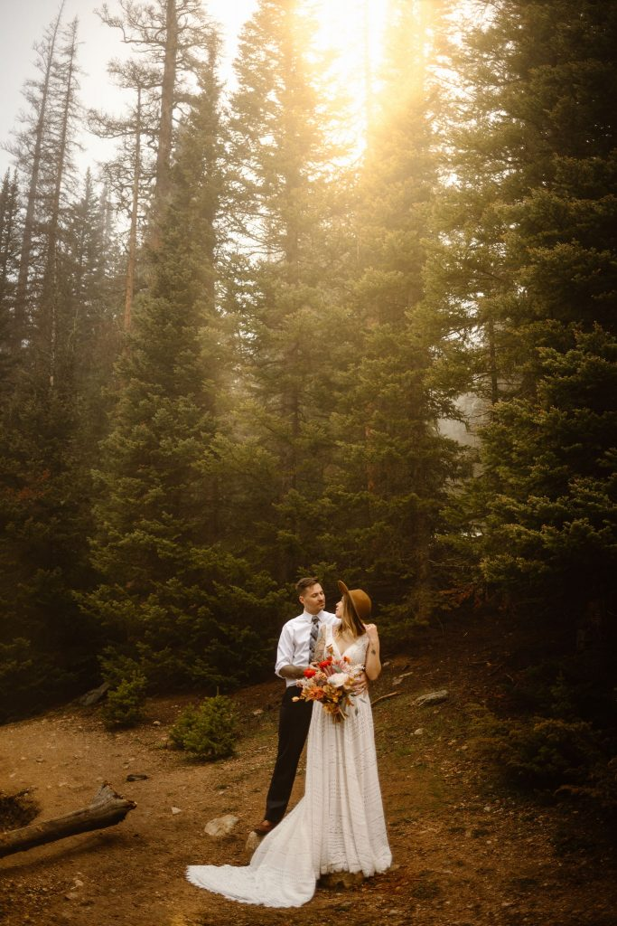 a couple standing in an evergreen forest wearing wedding clothes with the sun shining behind them