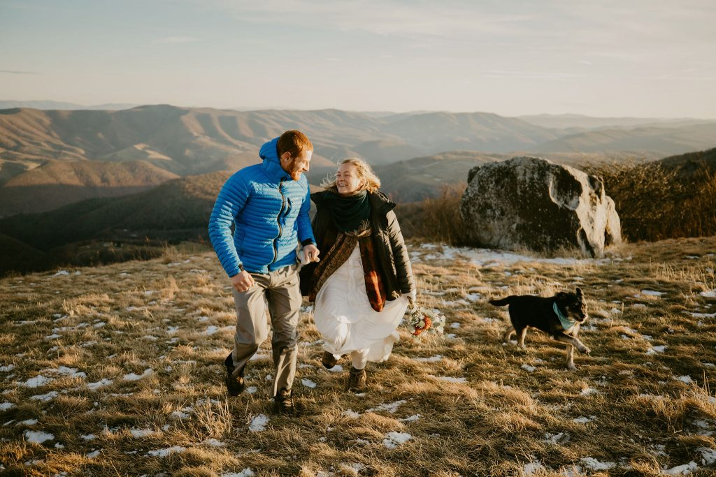 a couple running towards the camera while holding hands along side their dog