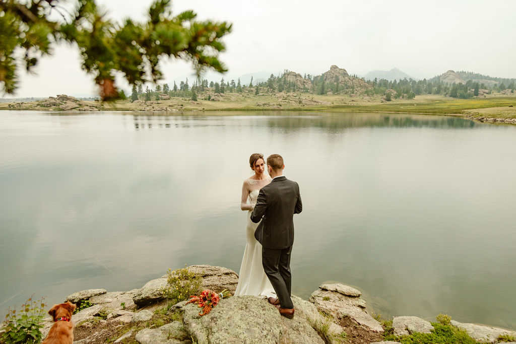 a couple wearing wedding clothes is standing on a rock next to a lake during their elopement ceremony in colorado