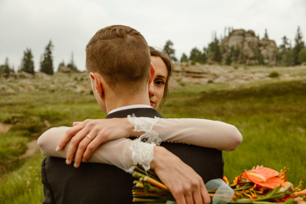 a couple hugging while wearing wedding attire in tall grass next to a lake