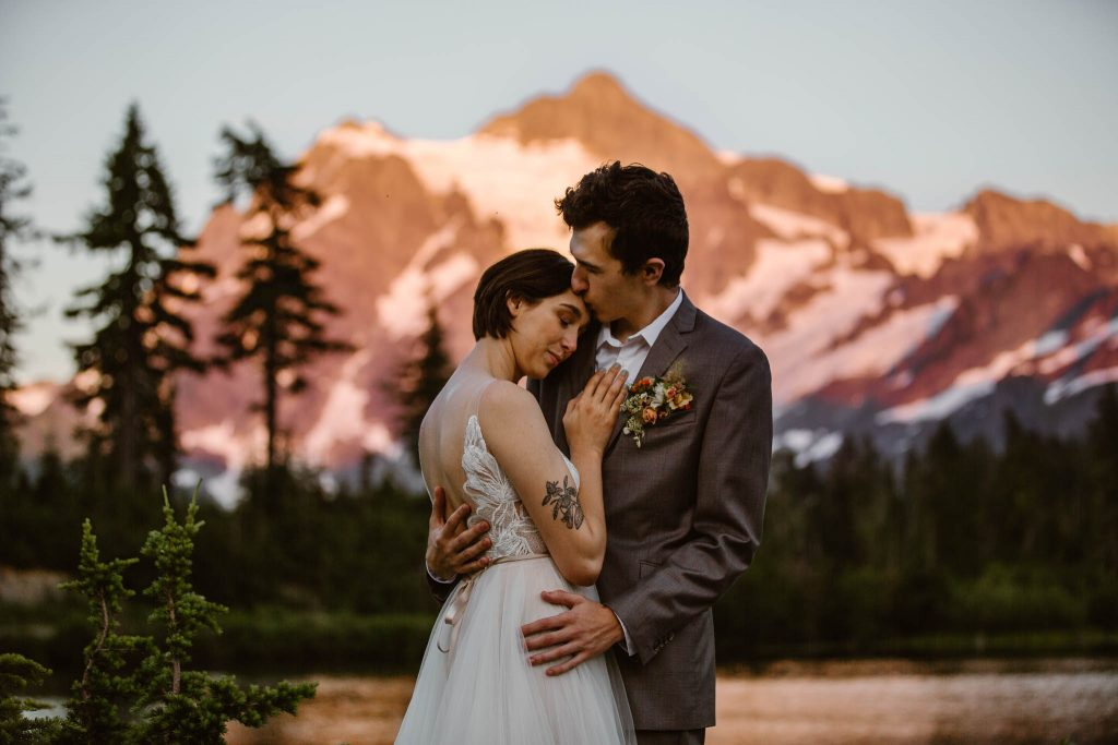 a bride and groom standing in front of a pink glowing mountain during their mountain elopement