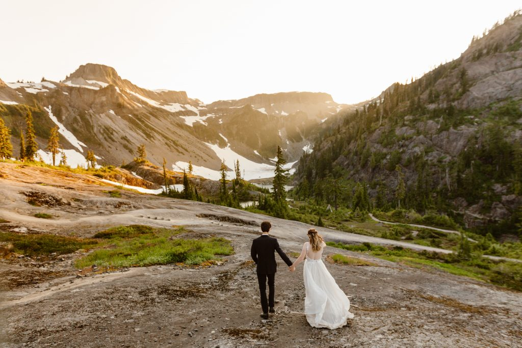 a bride and groom walking away from the camera towards a snow covered mountain while wearing wedding clothing