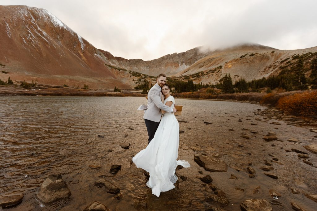 a bride and groom wearing traditional wedding attire are standing on a rock in an alpine lake in Colorado during their elopement ceremony