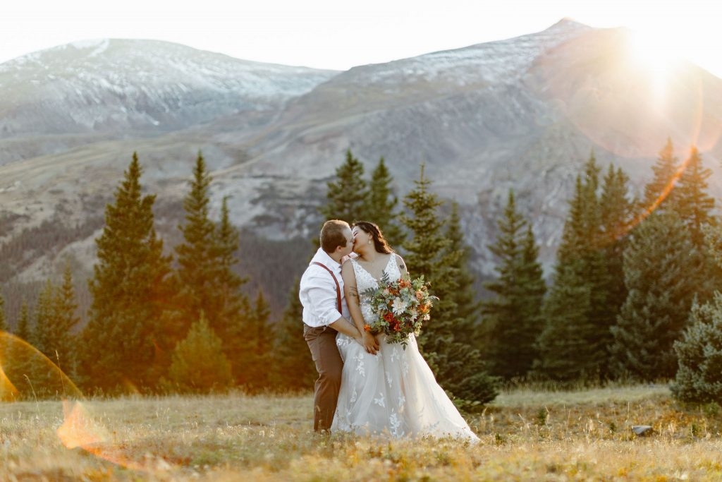 a bride and groom are wearing wedding attire and posing in front of a mountain during sunset during their breckenridge colorado elopement