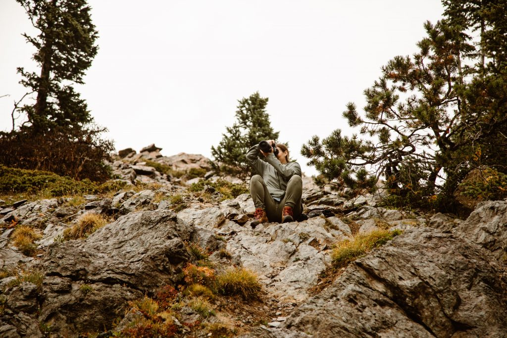 kelly shoul crouching down on the side of a mountain with a professional camera while wearing hiking attire