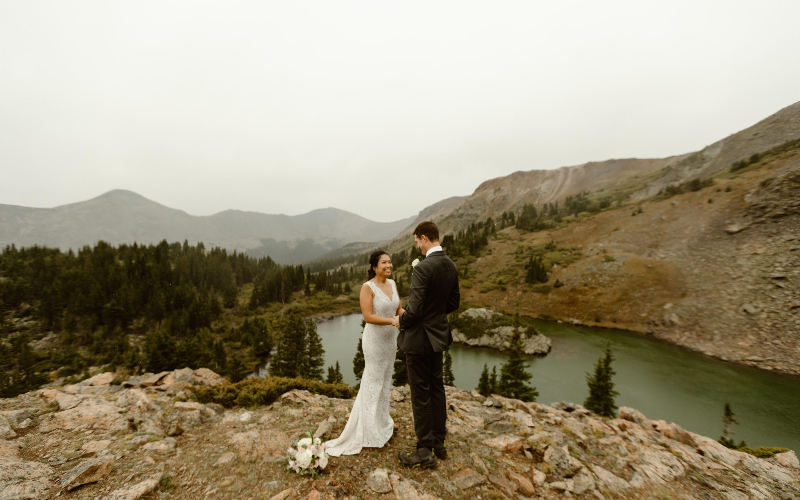 a bride and groom wearing wedding clothes are standing on top of a mountain during their elopement ceremony