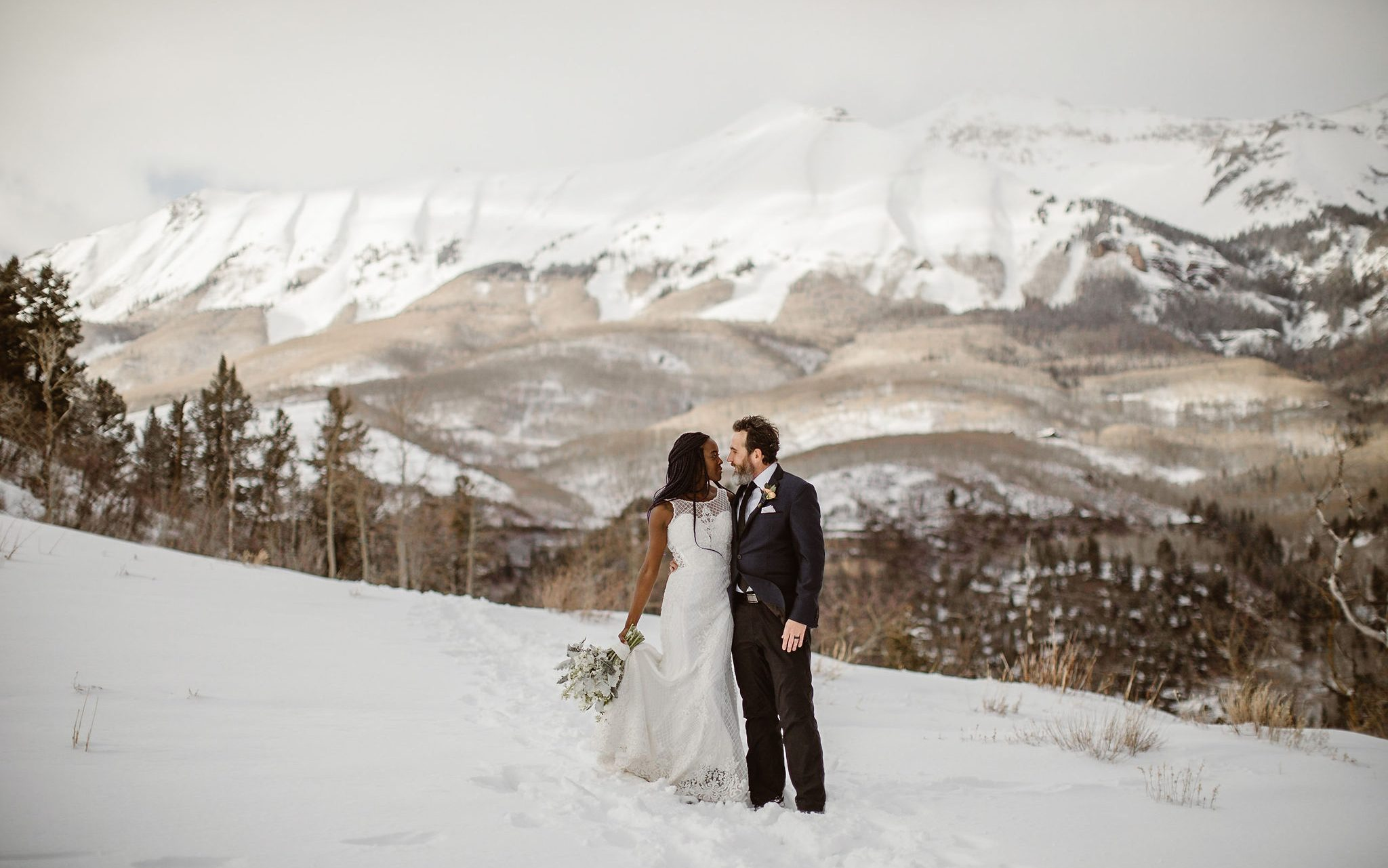 a bride wearing a white glittery wedding gown and groom wearing a black and navy blue tux are standing in snow with a snow covered mountain in the background