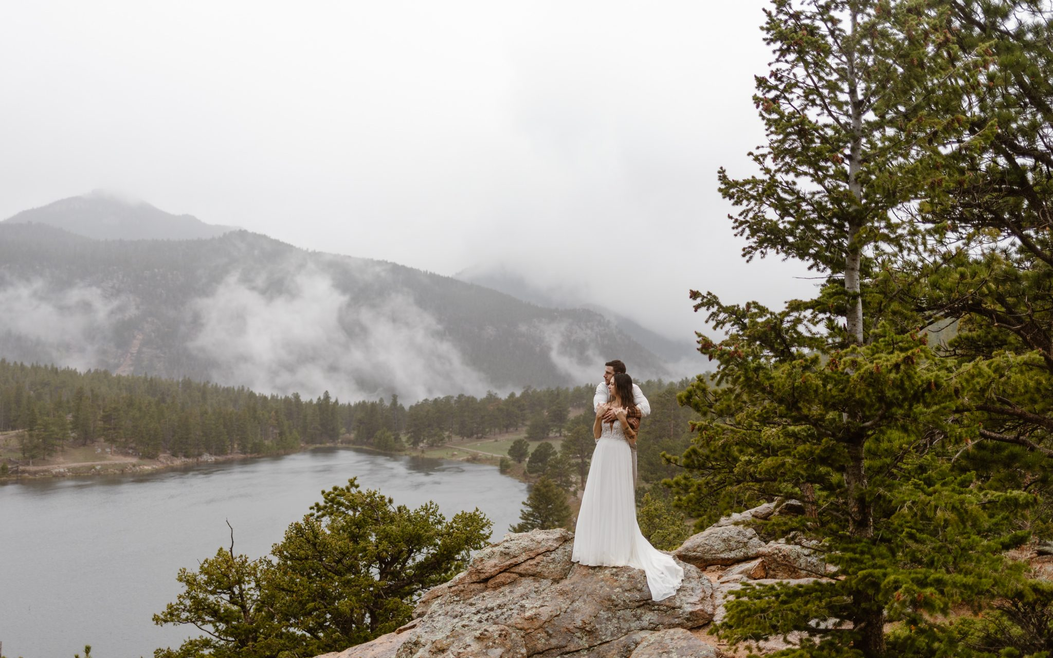 a couple wearing white and tan wedding clothes standing on top of a mountain ridge with a lake and evergreen forest in the background